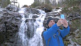 Ένα άτομο ταξιδεύει με ένα σακίδιο πλάτης κατά μήκος των διαδρομών βουνών Έφτασε στον όμορφο καταρράκτη και παίρνει ένα selfie στ φιλμ μικρού μήκους