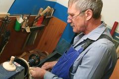 Ένα άτομο της ηλικίας συνταξιοδότησης με τα γυαλιά και ένα mustache χειρίζεται ένα ξύλινο κομμάτι προς κατεργασία σε έναν τόρνο Ο στοκ εικόνες με δικαίωμα ελεύθερης χρήσης