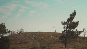 Ένα άτομο τρέχει σε ένα βουνό με μια καναδική σημαία στο χέρι του Η σημαία του Καναδά αναπτύσσεται στον αέρα απόθεμα βίντεο