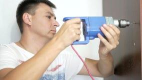 Ένα άτομο τρυπά μια τρύπα στο ντουλάπι με τρυπάνι απόθεμα βίντεο
