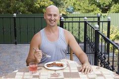 Ένα άτομο τρώει το κρέας από ένα οβελίδιο Στοκ φωτογραφία με δικαίωμα ελεύθερης χρήσης