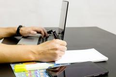 Ένα άτομο τυπώνει σε ένα lap-top, δίπλα στο τηλέφωνο, ταμπλέτα glasse στοκ εικόνες με δικαίωμα ελεύθερης χρήσης
