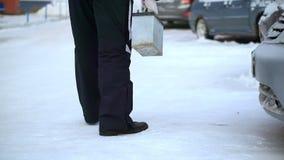 Ένα άτομο φέρνει ένα σπίτι μπαταριών αυτοκινήτων Είναι πολύ κρύο εξωτερικό απόθεμα βίντεο