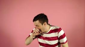 Ένα άτομο φτερνίζεται βαριά στεμένος σε ένα ρόδινο υπόβαθρο φιλμ μικρού μήκους