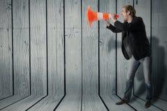 Ένα άτομο χρησιμοποιεί έναν κώνο προειδοποίησης ως megaphone Στοκ Φωτογραφία