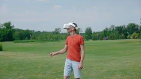 Ένα άτομο χρησιμοποιώντας μια κάσκα VR και παίζοντας ένα εικονικό παιχνίδι στο πάρκο φιλμ μικρού μήκους