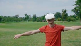 Ένα άτομο χρησιμοποιώντας μια κάσκα VR και παίζοντας ένα εικονικό παιχνίδι στο πάρκο απόθεμα βίντεο