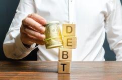 Ένα άτομο χτυπά κάτω τον πύργο με το χρέος λέξης με τη βοήθεια μιας δέσμης των χρημάτων Η πρόωρη επιστροφή του δανείου, αφαιρεί τ στοκ εικόνα με δικαίωμα ελεύθερης χρήσης