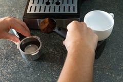 Ένα άτομο χύνει ένα τεμαχισμένο μετρώντας κουτάλι καφέ Στοκ Εικόνες