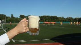 Ένα άτομο χύνει την μπύρα σε ένα ποτήρι στα πλαίσια ενός γηπέδου ποδοσφαίρου όπου παίζουν το ποδόσφαιρο, κινηματογράφηση σε πρώτο φιλμ μικρού μήκους