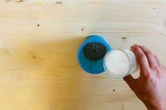 Ένα άτομο χύνει το γάλα από ένα ποτήρι σε έναν μπλε δονητή για να ανακατώσει την πρωτεΐνη Πρωτεΐνη ορρού γάλακτος, ένας υγιής τρό στοκ εικόνες
