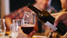 Ένα άτομο χύνει το κρασί στα ποτήρια Άνθρωποι που μιλούν στο υπόβαθρο απόθεμα βίντεο