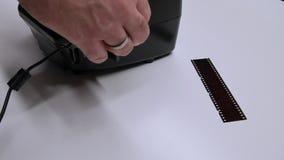 Ένα άτομο ψηφιοποιεί μια ταινία καμερών σε μια συσκευή φιλμ μικρού μήκους