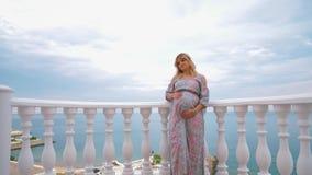 Ένα έγκυο κορίτσι στέκεται στο μπαλκόνι δίπλα στη θάλασσα και την χαϊδεύει tummy 4K απόθεμα βίντεο