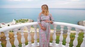 Ένα έγκυο κορίτσι στέκεται στο μπαλκόνι δίπλα στη θάλασσα και την χαϊδεύει tummy 4K φιλμ μικρού μήκους