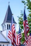 Ένα έθνος κάτω από το Θεό - αμερικανικές σημαίες μπροστά από το άσπρο καμπαναριό εκκλησιών Στοκ Φωτογραφίες