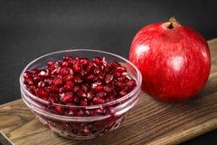 Ένα έντερο των σπόρων ροδιών εκτός από ολόκληρα φρούτα ροδιών Στοκ Εικόνα