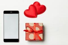 Ένα έξυπνα τηλέφωνο και ένα δώρο Στοκ φωτογραφία με δικαίωμα ελεύθερης χρήσης