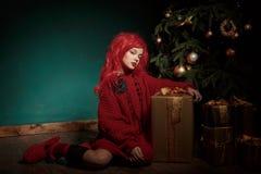 Ένα έφηβη σε ένα κόκκινες πλεκτές πουλόβερ και μια περούκα κάθεται στο πάτωμα κοντά σε ένα χριστουγεννιάτικο δέντρο και παρουσιάζ Στοκ Φωτογραφία