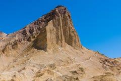 Ένα ίχνος πεζοπορίας διαβαίνει τη βάση μιας υψηλής αιχμής βουνών ερήμων σε ένα απέραντο ζωηρόχρωμο τοπίο ερήμων στοκ εικόνα