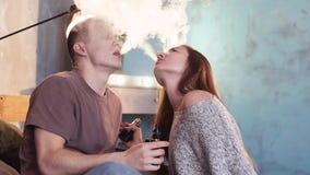 Ένα αγαπώντας ζεύγος σε ένα κρεβάτι καπνίζει τα ηλεκτρονικά τσιγάρα φιλμ μικρού μήκους