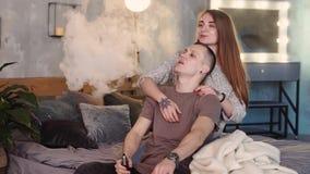 Ένα αγαπώντας ζεύγος σε ένα κρεβάτι καπνίζει τα ηλεκτρονικά τσιγάρα απόθεμα βίντεο
