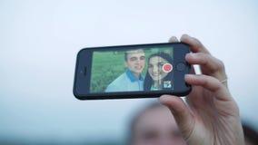 Ένα αγαπώντας ζεύγος χρησιμοποιεί ένα smartphone προκειμένου να καταληφθεί σε ένα smartphone Selfie στο τηλέφωνο απόθεμα βίντεο