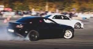 Ένα αγωνιστικό αυτοκίνητο κλίσης στη δράση με τις καπνίζοντας ρόδες παρουσιάζει στοκ φωτογραφία
