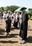Ένα αγόρι εξετάζει ένα άτομο στο κοστούμι γιατρών πανούκλας στο φεστιβάλ αναγέννησης Στοκ Εικόνα