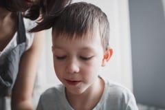 Ένα αγόρι 8 ετών ενδιαφέρεται για την προσοχή mom της εργασίας ` s στην κουζίνα στοκ φωτογραφία