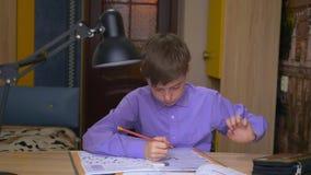 Ένα αγόρι εφήβων κάνει την εργασία Μακρινή εκπαίδευση Εκπαίδευση στο σπίτι φιλμ μικρού μήκους