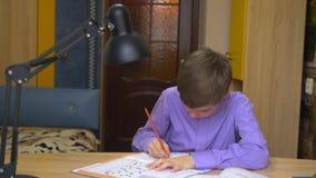 Ένα αγόρι εφήβων κάνει την εργασία Μακρινή εκπαίδευση Εκπαίδευση στο σπίτι απόθεμα βίντεο