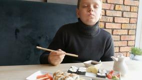 Ένα αγόρι εφήβων παίρνει το ρόλο σουσιών με τα κινεζικά ραβδιά και τις πτώσεις μπαμπού που στη σάλτσα σόγιας, παίρνει ένα κομμάτι φιλμ μικρού μήκους
