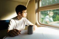 Ένα αγόρι εφήβων στα γυαλιά σε ένα τραίνο κάθεται σε έναν πίνακα με το τσάι στοκ εικόνες με δικαίωμα ελεύθερης χρήσης