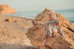 Ένα αγόρι κάθεται στην παραλία σε ένα ριγωτό πουκάμισο με θαλάσσιο έναν lifebuoy, liferound Ένα αγόρι κάθεται στην άμμο σε μια όμ Στοκ φωτογραφία με δικαίωμα ελεύθερης χρήσης