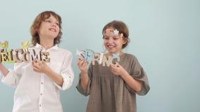 Ένα αγόρι και ένα άλμα κοριτσιών, χορεύουν και έχουν τη διασκέδαση στο στούντιο σε ένα μπλε υπόβαθρο με το ντεκόρ άνοιξη στα χέρι απόθεμα βίντεο