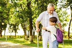 Ένα αγόρι και ένας ηληκιωμένος στα δεκανίκια περπατούν στο πάρκο Το αγόρι κρατά το παλαιό χέρι ατόμων ` s Στοκ Εικόνα