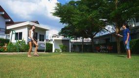 Ένα αγόρι και ένα κορίτσι εφήβων παίζουν το μπάντμιντον σε έναν πράσινο χορτοτάπητα στο κατώφλι του σπιτιού τους απόθεμα βίντεο
