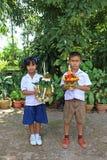 Ένα αγόρι και ένα κορίτσι κρατούν ότι διακοσμήστε το δίσκο βάθρων στοκ φωτογραφία