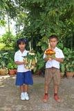 Ένα αγόρι και ένα κορίτσι κρατούν ότι διακοσμήστε το δίσκο βάθρων στοκ φωτογραφία με δικαίωμα ελεύθερης χρήσης