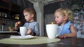Ένα αγόρι και ένα κορίτσι πίνουν το τσάι από τις μεγάλες κούπες στην οικογενειακή κουζίνα και τρώνε croissants ευρωπαϊκό εσωτερικ φιλμ μικρού μήκους