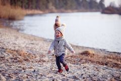 Ένα αγόρι και ένα κορίτσι που έχουν τη διασκέδαση έξω την πρώιμη άνοιξη στο δάσος κοντά στο νερό Μια αδελφή και brothe από κοινού στοκ εικόνα