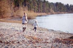 Ένα αγόρι και ένα κορίτσι που έχουν τη διασκέδαση έξω την πρώιμη άνοιξη στο δάσος κοντά στο νερό Μια αδελφή και brothe από κοινού στοκ φωτογραφία