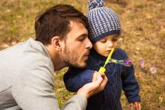 Ένα αγόρι και ο μπαμπάς του, φύσηγμα βράζουν έξω Στοκ εικόνες με δικαίωμα ελεύθερης χρήσης