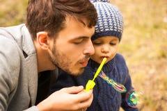 Ένα αγόρι και ο μπαμπάς του, φύσηγμα βράζουν έξω Στοκ Εικόνες