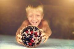 Ένα αγόρι κρατά ψηλά ένα πιάτο του κουάκερ με τους νωπούς καρπούς Εστίαση στο πιάτο του κουάκερ Στοκ Εικόνες