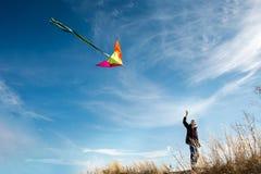 Ένα αγόρι με έναν ικτίνο ενάντια στο μπλε ουρανό r Ευρωπαϊκό αγόρι εμφάνισης Κίτρινη χλόη στοκ φωτογραφίες