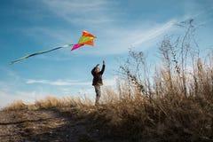 Ένα αγόρι με έναν ικτίνο ενάντια στο μπλε ουρανό r Ευρωπαϊκό αγόρι εμφάνισης Κίτρινη χλόη στοκ φωτογραφία με δικαίωμα ελεύθερης χρήσης