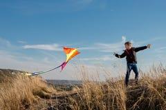 Ένα αγόρι με έναν ικτίνο ενάντια στο μπλε ουρανό r Ευρωπαϊκό αγόρι εμφάνισης Κίτρινη χλόη στοκ φωτογραφία