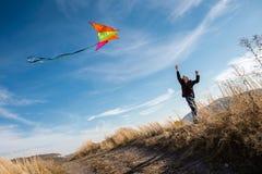 Ένα αγόρι με έναν ικτίνο ενάντια στο μπλε ουρανό r Ισχυρός άνεμος Ένα αγόρι της ευρωπαϊκής εμφάνισης, έντυσε στα τζιν και το Μαύρ στοκ φωτογραφία